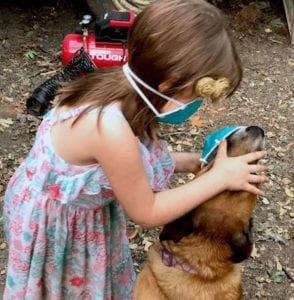Small girl putting dust mask on her dog